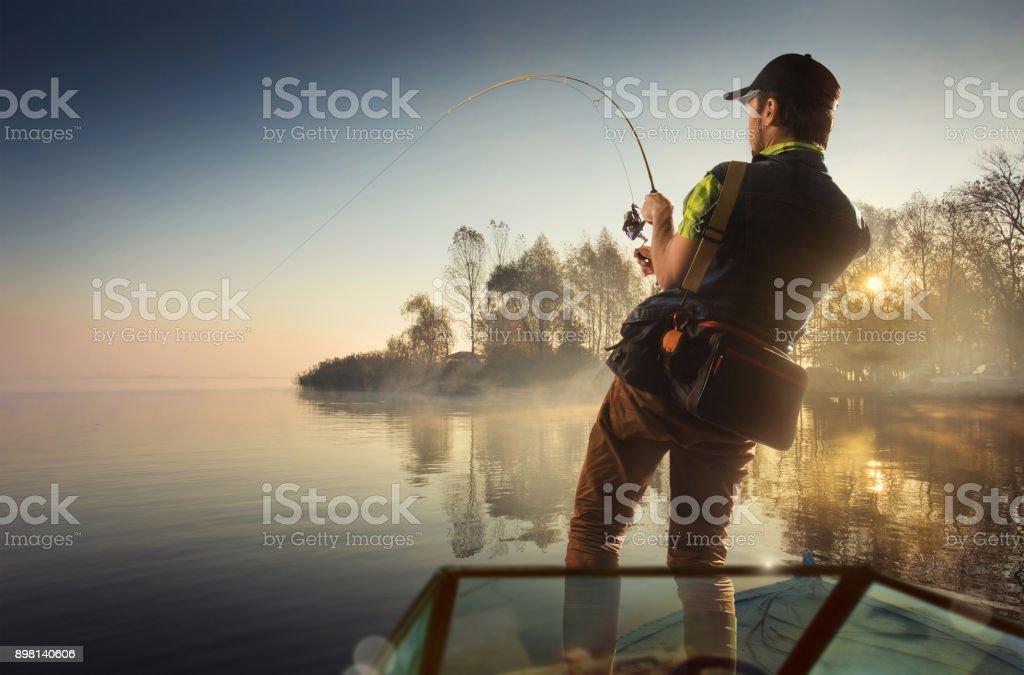 Fishing. Man fishing on a lake on boat stock photo