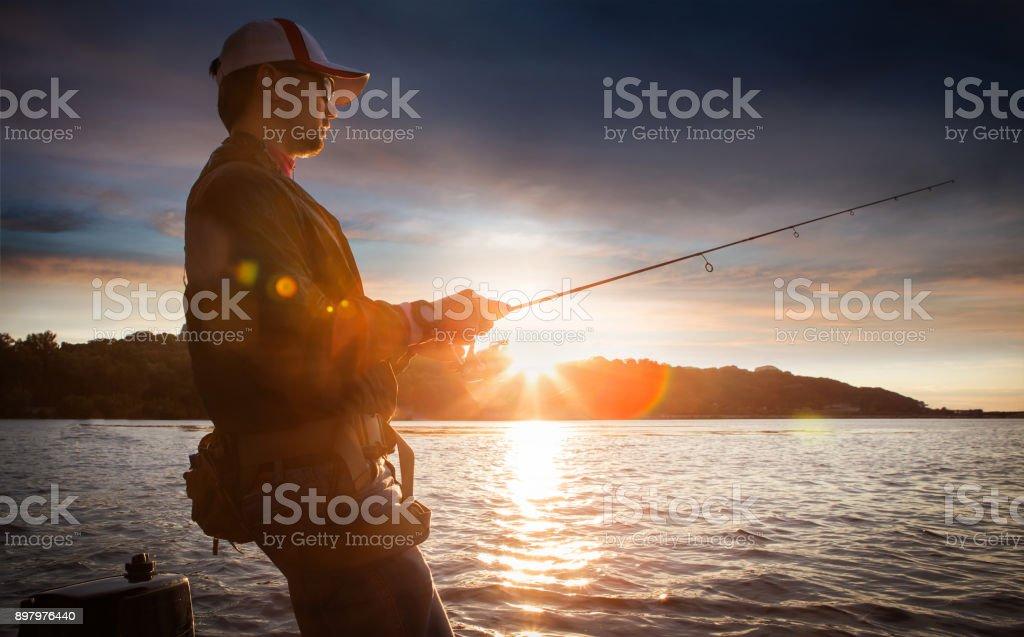 Fishing. Man fishing on a lake. Sunset stock photo
