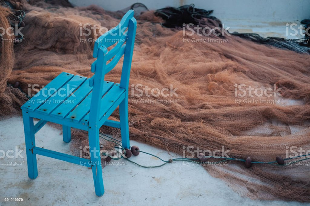 Fishing net and blue chair stock photo