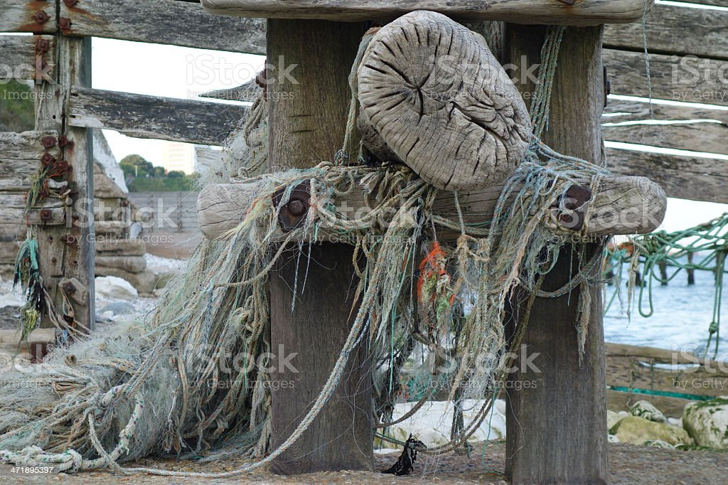 fishing net caught around a sea defence stock photo
