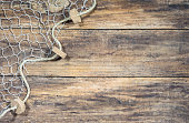 istock Fishing net over rustic wooden background 895778592