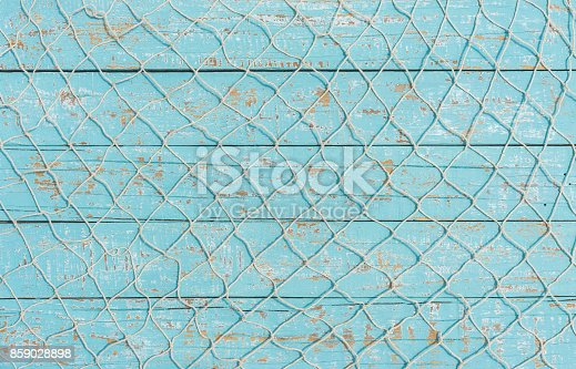 istock Fishing net texture over light blue wood, maritime background 859028898