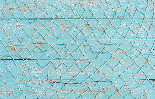 Fishing net texture over light blue wood, maritime background