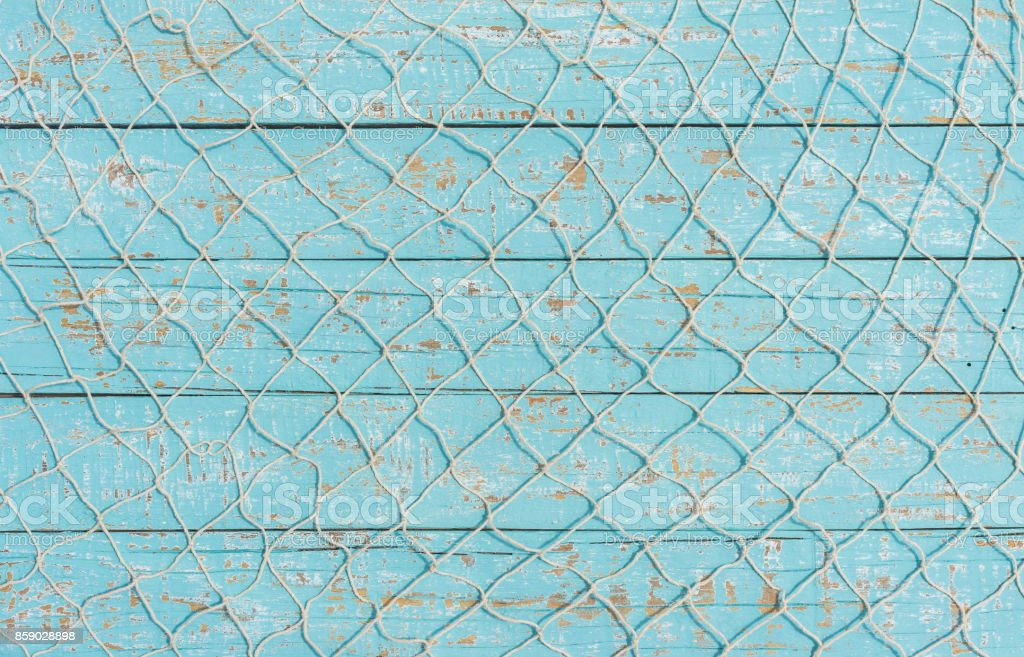 Fishing net texture over light blue wood, maritime background stock photo