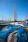In this photo you can see the Palma's Harbour in a sunny day with some fishing nets and a lot of sailing boats in the backgrounds