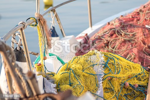Fishing nets and tackle stored on the deck of a small inshore fishing boat.  Port Anna, Sithonia, Greece.