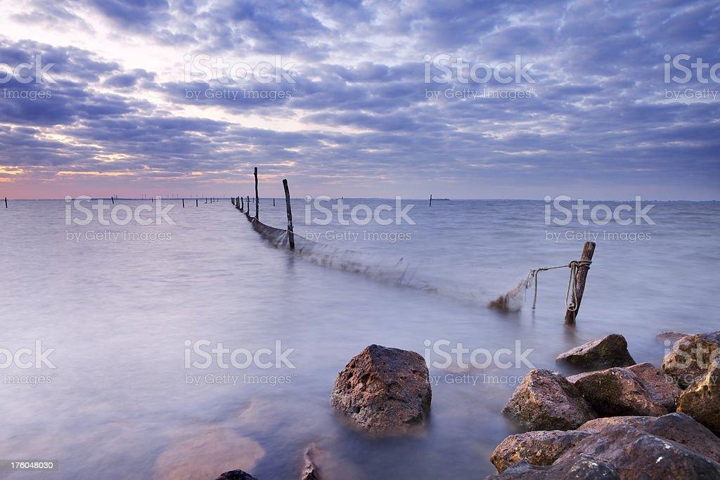 Fishing nets in lake at sunrise near Durgerdam, The Netherlands royalty-free stock photo