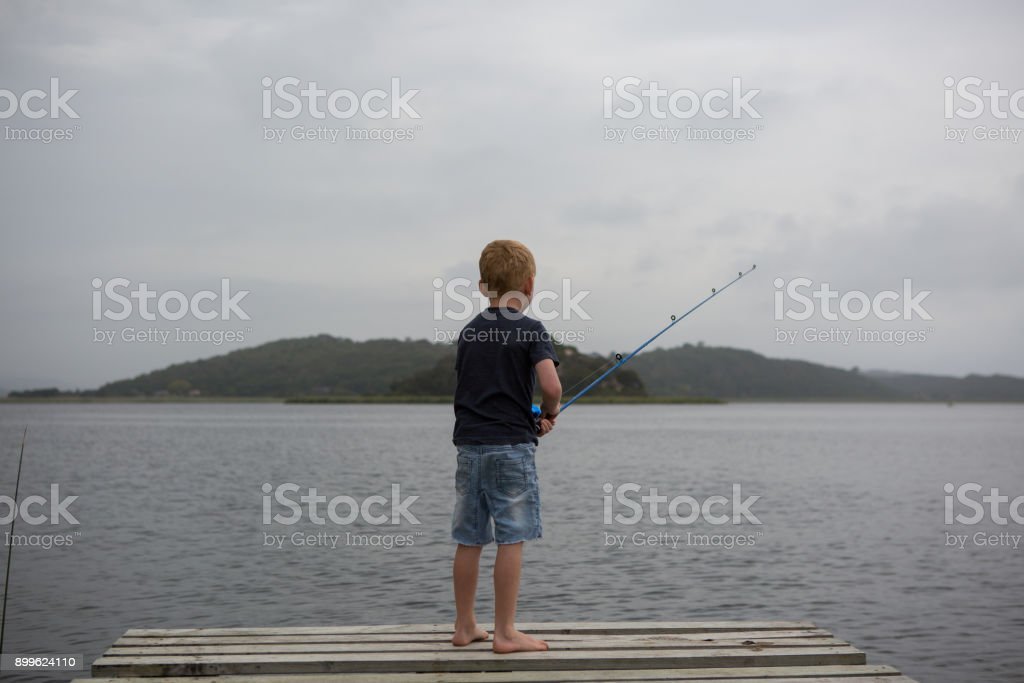 Fishing off the wooden jetty at the lake stock photo