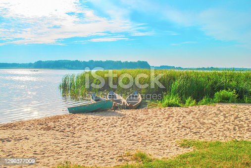 Fishing old wooden boats moored on lake by blue sky, sunny light day. Summer landscape and vintage empty woods ship on sandy beach and green reeds, soft selective focus