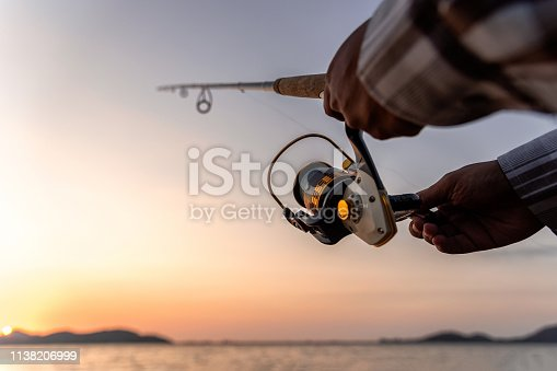 Fishing on the lake at sunset. Closeup spinning in the male hand, Fishing background.