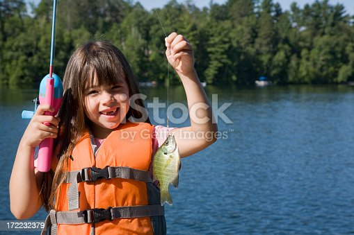 A little girl is holding up her sunfish catch.  With copyspace.