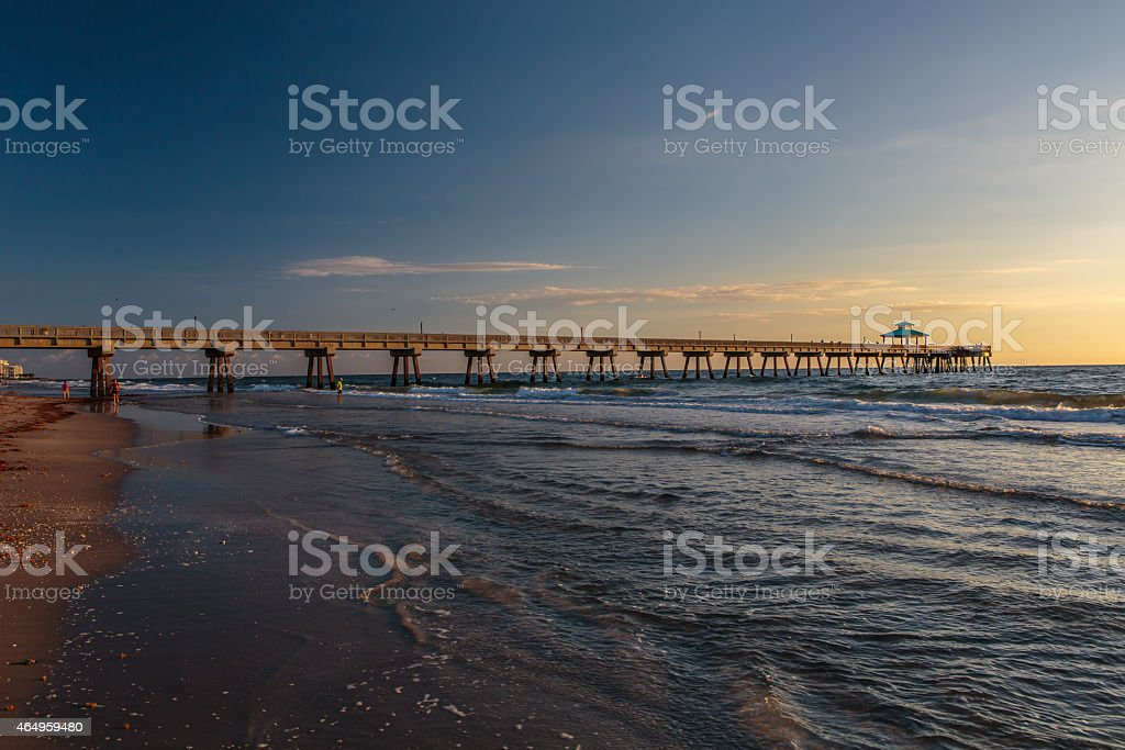 Fishing Pier at Sunrise with Blue Sky and White Clouds The first light of day shines on a fishing pier in Deerfield Beach Florida. The blue sky, white clouds, and ocean reflect the rich warm light of the morning. 2015 Stock Photo