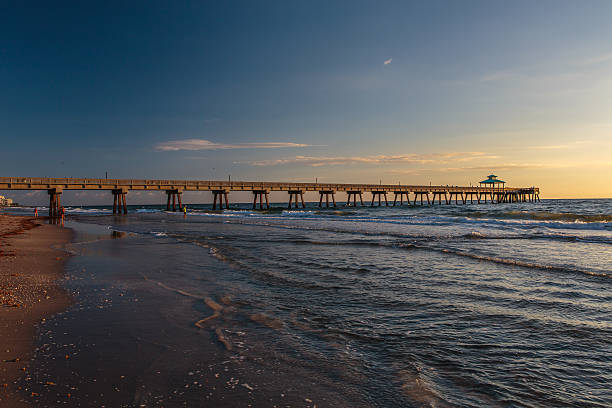 Fishing Pier at Sunrise with Blue Sky and White Clouds stock photo