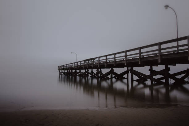 Fishing pier disappearing into the sea in foggy conditions.