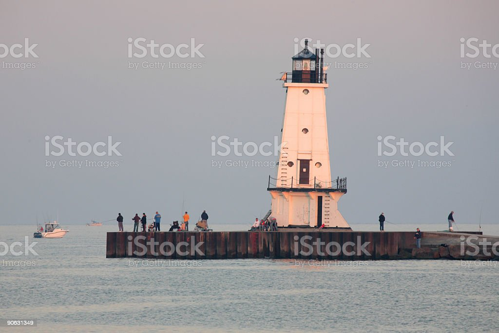 Fishing Pier, Fisherman and Lighthouse royalty-free stock photo