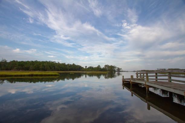 a fishing pier into a sea of tranquil, reflective waters. - estuário imagens e fotografias de stock