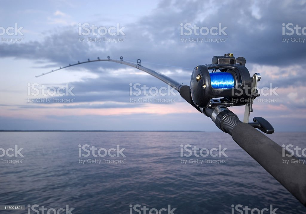 A fishing pole and a beautiful sunset on the ocean stock photo