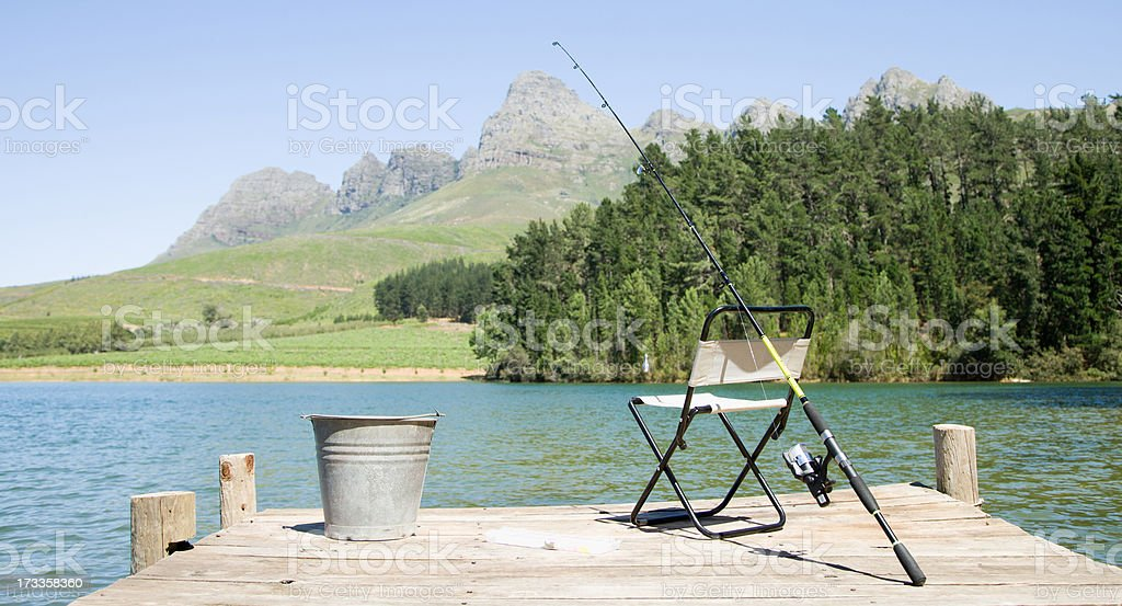 Fishing pole and chair on dock stock photo