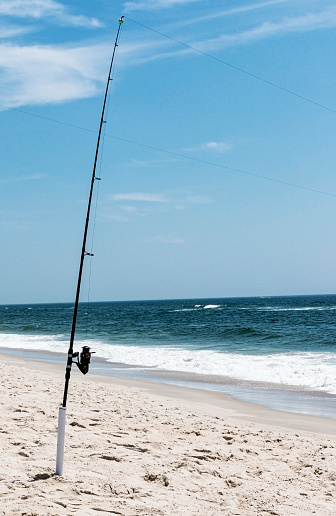 istock Fishing pole standing in holder on beach at the Ocean 1267506601