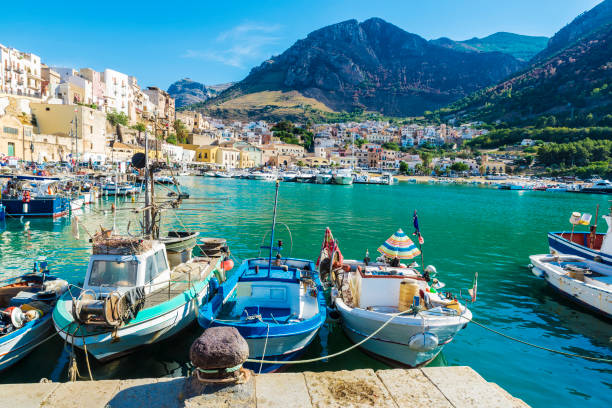 Fishing port with old wooden fishing boats in Sicily, Italy Fishing port with old wooden fishing boats docked at the marina in summer in Castellammare del Golfo in Sicily, Italy sicily stock pictures, royalty-free photos & images