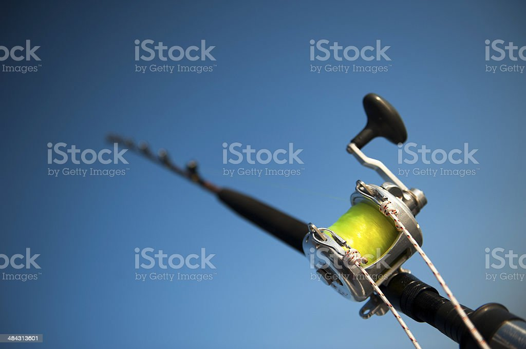 Fishing reel and rod on blue sky stock photo