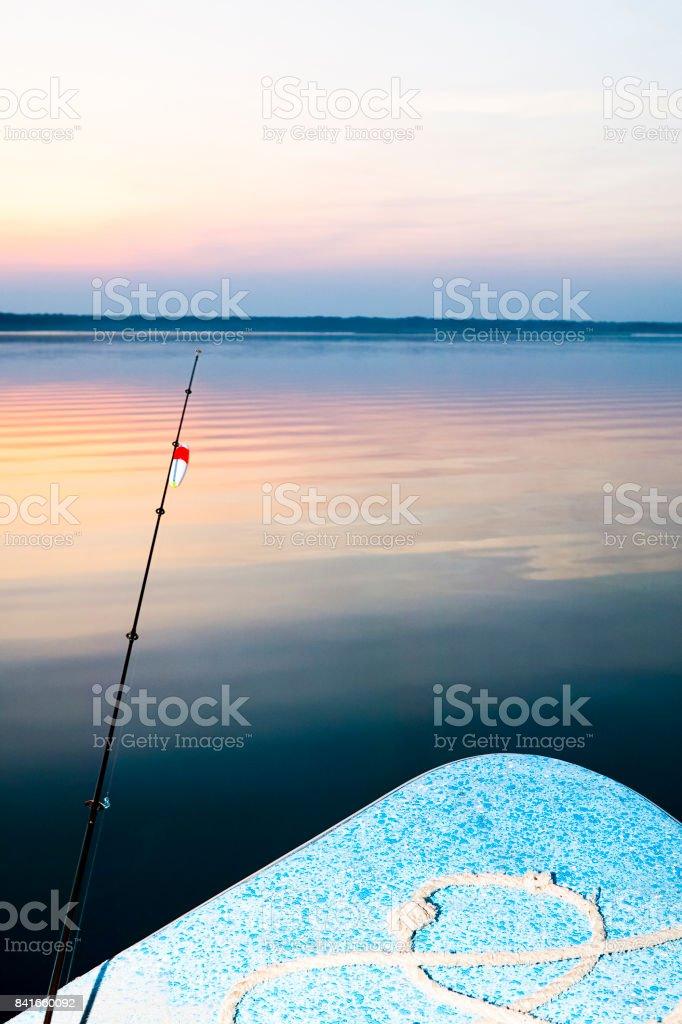 Fishing rod against calm lake stock photo