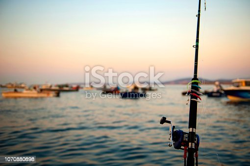 1094918172 istock photo Fishing rod and fishing boats on sunset 1070880898