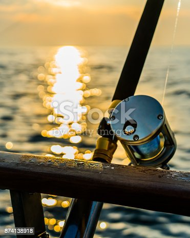 istock Fishing rod and reel on boat 874138918