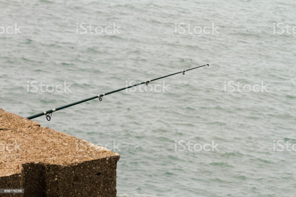 fishing rod on a rock facing the sea stock photo more pictures of