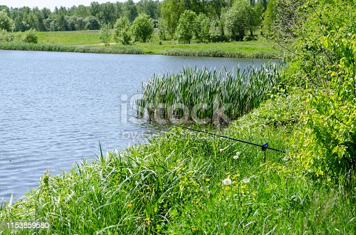 1094918172 istock photo Fishing rod on the background lake. 1153859580