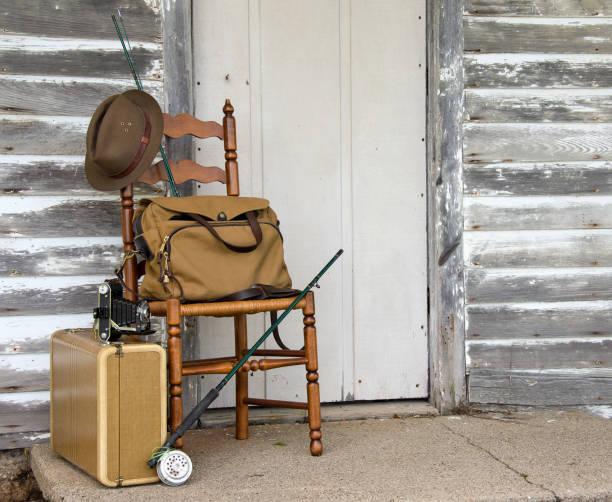 fishing rod on wooden chair with hat - angelkoffer stock-fotos und bilder
