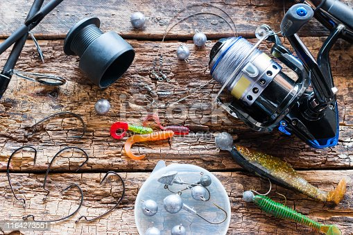 Kurgan, Russia, June 10, 2019 fishing rod spinning, fishing tackle and bait on wooden background