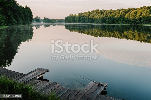 1094918172 istock photo Fishing rod, spinning reel on the background pier river bank. Sunrise. Fog against the backdrop of lake. Misty morning. wild nature. The concept of rural getaway. Article about fishing day. 1092160594