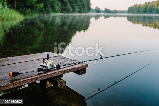 1094918172 istock photo Fishing rod, spinning reel on the background pier river bank. Sunrise. Fog against the backdrop of lake. Misty morning. wild nature. The concept of rural getaway. Article about fishing day. 1092160602
