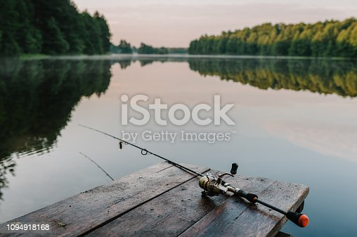 1094918172 istock photo Fishing rod, spinning reel on the background pier river bank. Sunrise. Fog against the backdrop of lake. Misty morning. wild nature. The concept of rural getaway. Article about fishing day. 1094918168