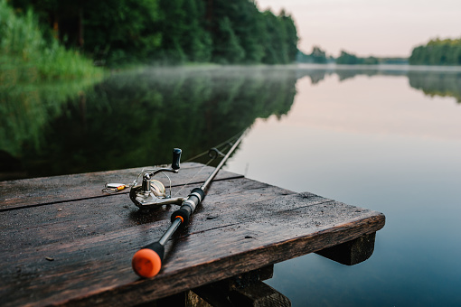 Fishing rod, spinning reel on the background pier river bank. Sunrise. Fog against the backdrop of lake. Misty morning. wild nature. The concept of rural getaway. Article about fishing day.