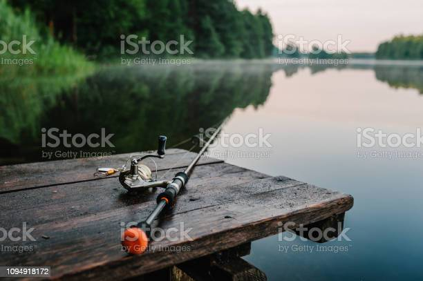 Photo of Fishing rod, spinning reel on the background pier river bank. Sunrise. Fog against the backdrop of lake. Misty morning. wild nature. The concept of rural getaway. Article about fishing day.