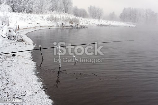 1094918172 istock photo Fishing rod spinning reel on the background pier river bank Sunrise Fog against the backdrop of lake Misty morning wild nature The concept of rural getaway Article about fishing day 1130233999