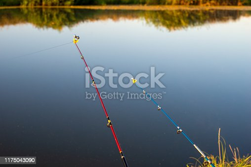 1094918172istockphoto Fishing rod, spinning reel, on the background quiet pond. 1175043090