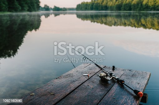 1094918172 istock photo Fishing rod, spoon, hooks on a brown wooden background. fishing bait. close up. throw-line. fishing rod. Rod on the bridge. Bridge passes through the lake, river. flat lay. top view. 1092160590