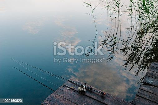 1094918172 istock photo Fishing rod, spoon, hooks on a brown wooden background. fishing bait. close up. throw-line. fishing rod. Rod on the bridge. Bridge passes through the lake, river. flat lay. top view. 1092160620