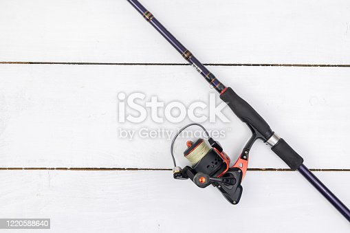 864720746 istock photo Fishing rod with a fishing reel above white wooden background. 1220588640