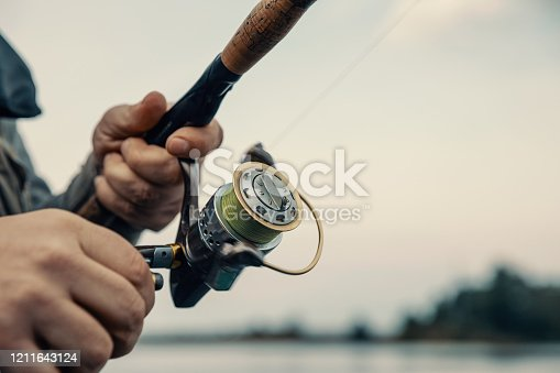 914030378 istock photo Fishing rod with a spinning reel in the hands of a fisherman. Fishing background. 1211643124