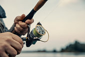 istock Fishing rod with a spinning reel in the hands of a fisherman. Fishing background. 1211643124