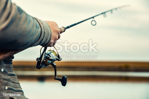914030378 istock photo Fishing rod with a spinning reel in the hands of a fisherman. Fishing background. 1211643166