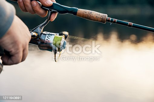 914030378 istock photo Fishing rod with a spinning reel in the hands of a fisherman. Fishing background. 1211643691
