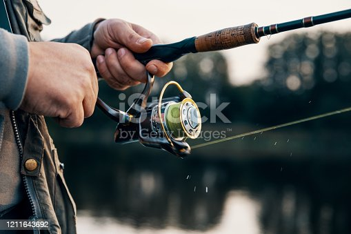 914030378 istock photo Fishing rod with a spinning reel in the hands of a fisherman. Fishing background. 1211643692