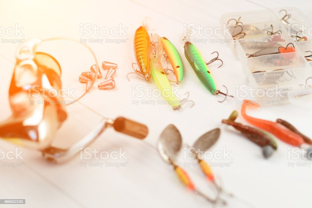 Fishing rod with reel, spoon baits, tackles and wobblers in box for catching or fishing a predatory fish on white vintage wooden background stock photo