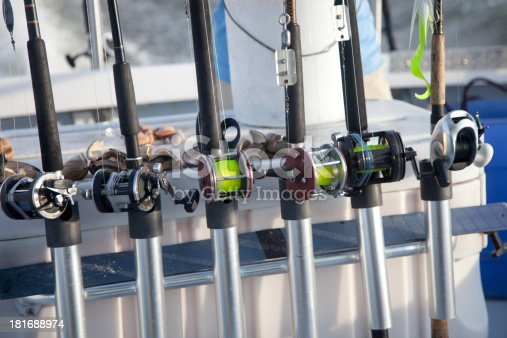 Fishing rods and bait laying on a table on a charter boat driving out to sea on a sunny day