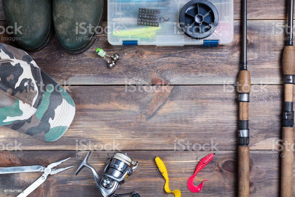 Fishing rods and reel with boots, cap and fishing tackles in a box on wooden background with free space royalty-free stock photo